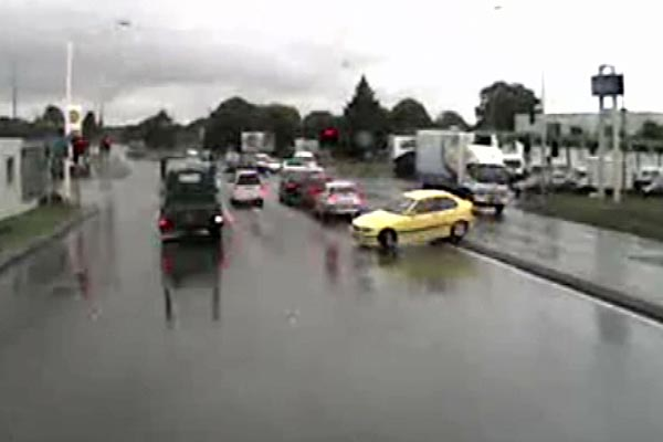 A yellow BMW mounts the median