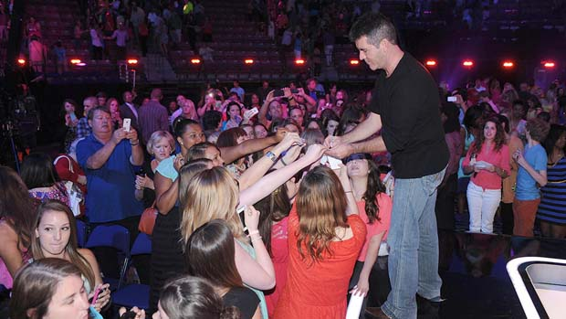ans at X FACTOR auditions mob Simon Cowell for his autograph.