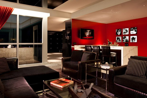 The suite has two bedrooms with mirrored cealings, black vinyl walls and an S&M table.