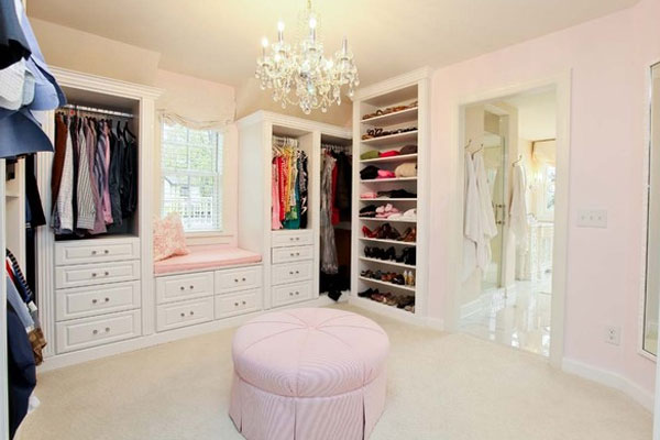 A soft-ice pink wall, chandelier and ottoman turns this large wardrobe room into a girl's dream boudoir