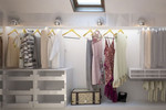 The greay walls work with soft lighting for a calming yet luxurious closet display