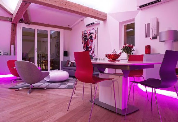A plain white room with white walls is stunningly transformed with a neon pink floor light