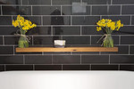 Striking black tiles have added warmth with a wood shelf