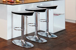 Black and white bar stools complement the colour in the dining area
