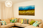 The warm colour of the sofa works very well with the colourful cushions and artwork.