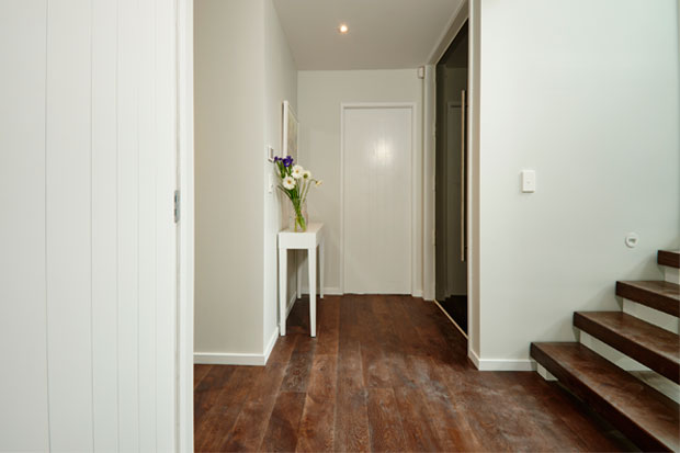 The dark wooden floors and the white walls in the entranceway are practical and create a welcoming athmosthere.