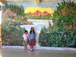 Jasmin and Khryzelle posing in front of their school's mural